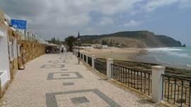 De boulevard is vrij recent aangelegd. Achter het parasolletje loop je ter hoogte van het strand naar het huis.  Goede restaurants (o.a. Chicca's!) op loopafstand. Op de achtergrond de imposante rotskust. Er loopt een mooi pad over de berg naar Lagos en Burgau en andere stranden (ong. 5km).