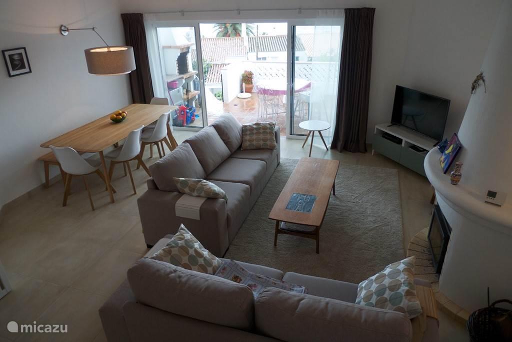 Ruime woonkamer met houtkachel, TV, schuifpui naar het terras met ingebouwde BBQ