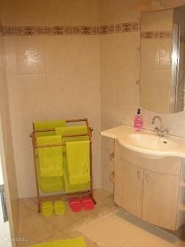 Mooie badkamer met wastafel en ligbad en douche-cabine.