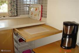 detail of kitchen with sliding cutting board. Also handy to put hot pans.