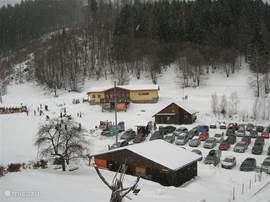 De parkeerplaats onderaan de berg,waarop villa Wladimir ligt, met een van de sleepliften.