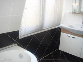 Badkamer op de verdieping: randje libad, raam en deels het badkamermeubel.