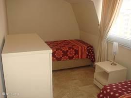 Dit is de tweede slaapkamer, met 2 x 1 persoonsbed, nachtkastje en ladenkast,