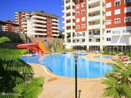 Groot zwembad met glijbanen en een kinderbad, rondom het zwembad zijn ligstoelen en parasols.