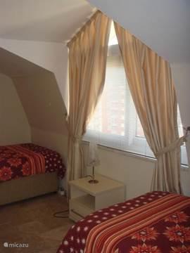 Tweede slaapkamer, vanuit de deur gezien: raam met luxaflex en verduisteringsgordijnen.
