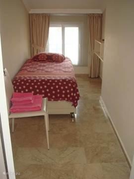 Eenpersoons slaapkamer: stoel, bed en raam met luxaflex en verduisteringsgordijnen.
