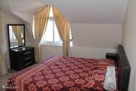 Grote slaapkamer met 2 x eenpersoonsbed, 2 nachtkastjes, toiletmeubel, raam en een schuifpui naar het terras.