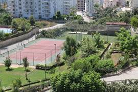 Tennisbaan met daarachter het voetbalveld.