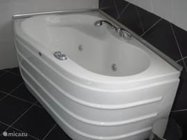 Jacuzzi ligbad in de badkamer op de verdieping.