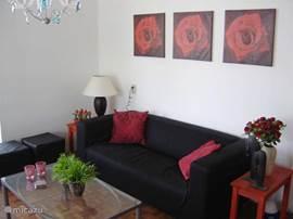 woonkamer voorzien van parketvloer, met moderne zithoek en kleuren TV