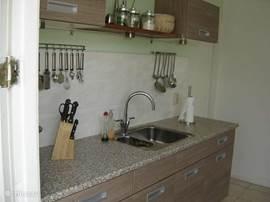 keuken met warm- en koudwaterkraan en luxe kookgerei uitgevoerd in rvs.