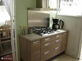 keuken met luxe rvs gaskookplaat en wokbrander, afzuigkap, combimagnetron, koelkast met diepvries, koffiezetapparaat, wa