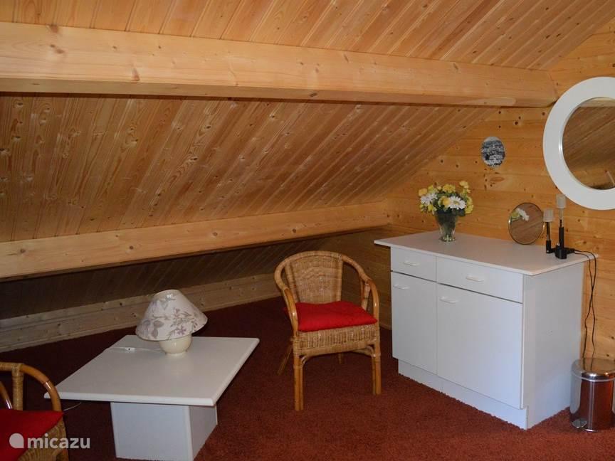 Zitje en spiegel op de slaapkamer boven. In het kastje liggen extra dekbedden en kussens.
