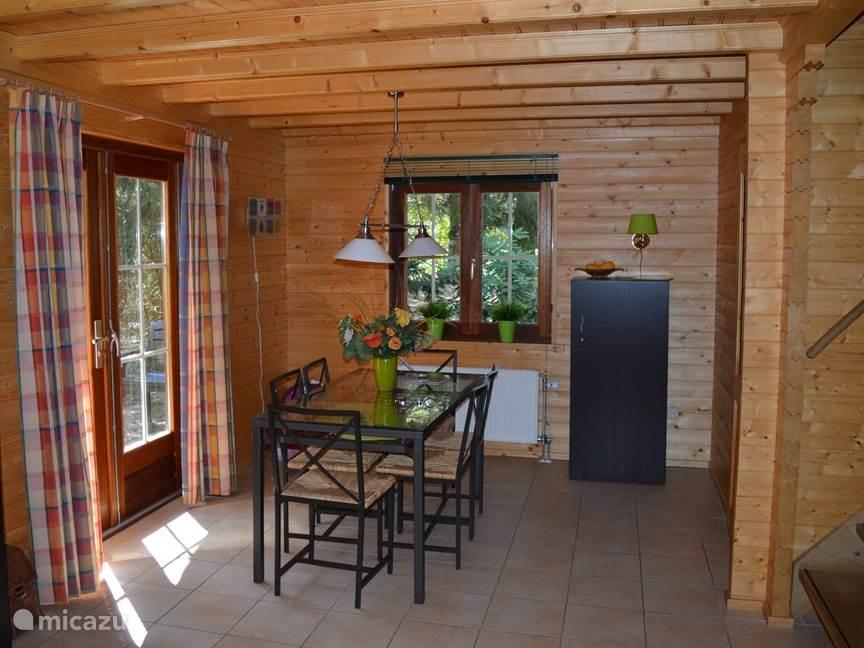 Deel van de woonkamer met openslaande deuren naar het terras. Eettafel met zes stoelen. Aan de rechterkant zie je de trap naar de slaapkamer boven.
