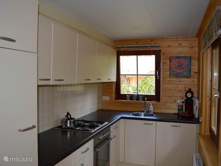 Moderne keuken met diverse inbouwapparatuur. Koelkast met klein vriesvakje, vaatwasmachine en oven. In de berging in de hal is ook een magnetron aanwezig.