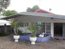 De achterzijde van het huis met het ruime terras en de koi karper vijver.