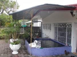 Aan de achterkant van het huis is het ruime terras, met de mooie rustgevende vijver met koi karpers.
