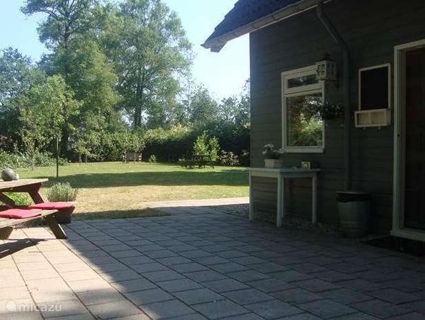 Het terras met uitzicht op de tuin met fruitbomen en vuurplaats.