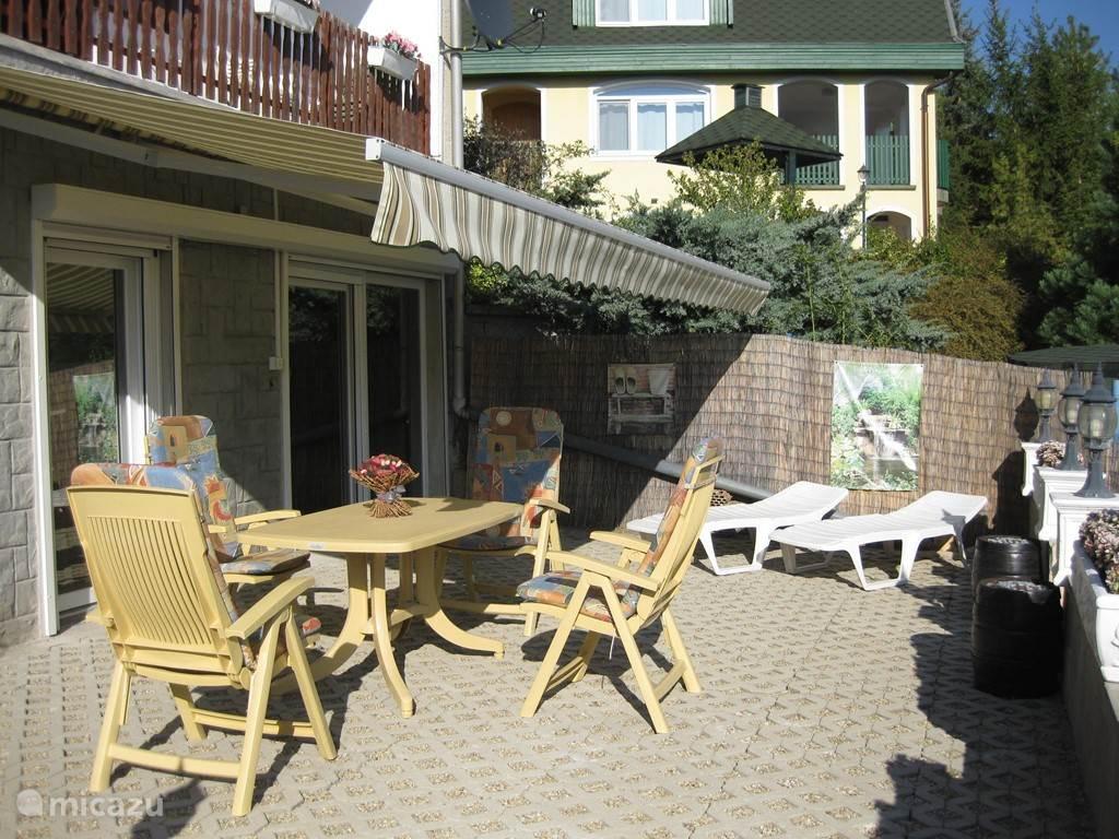 De terrasstoelen, tafel en parasol op het terras.