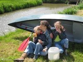 Moeder en kinders bij de kano