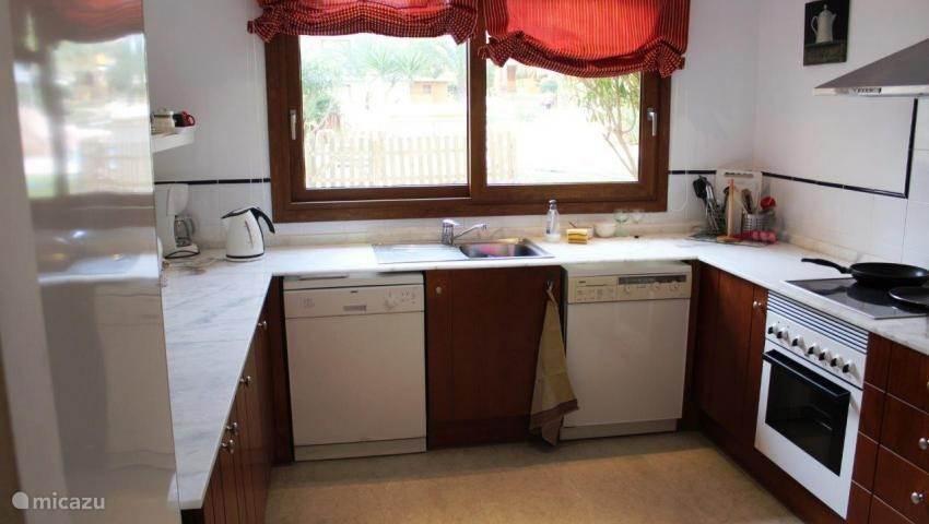 De uitgebreide keuken met vaatwasser, wasmachine, oven en koelkast.