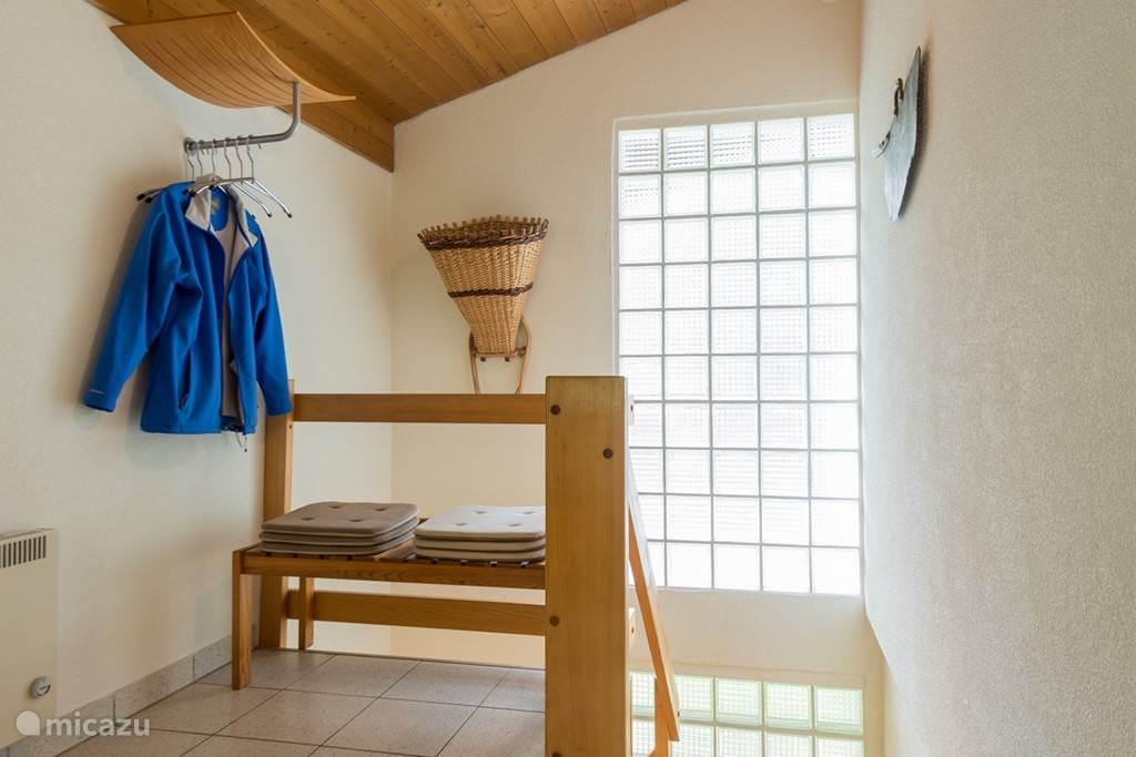 De ruime entreehal van Stella Alpina Oost op het woonniveau met trap naar de grote slaapkamer en doucheruimte