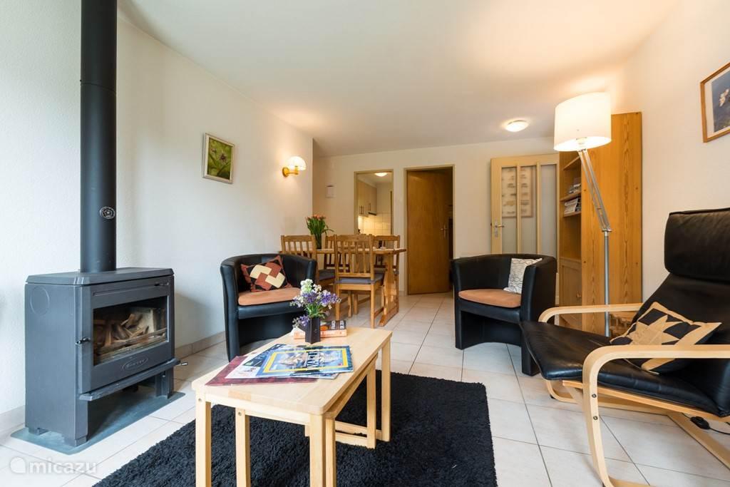 De woonkamer met zicht naar de keuken. De zithoek met gezellige haardkachel is in de herfst en winter een gezellig centraal punt met heerlijke warmte.