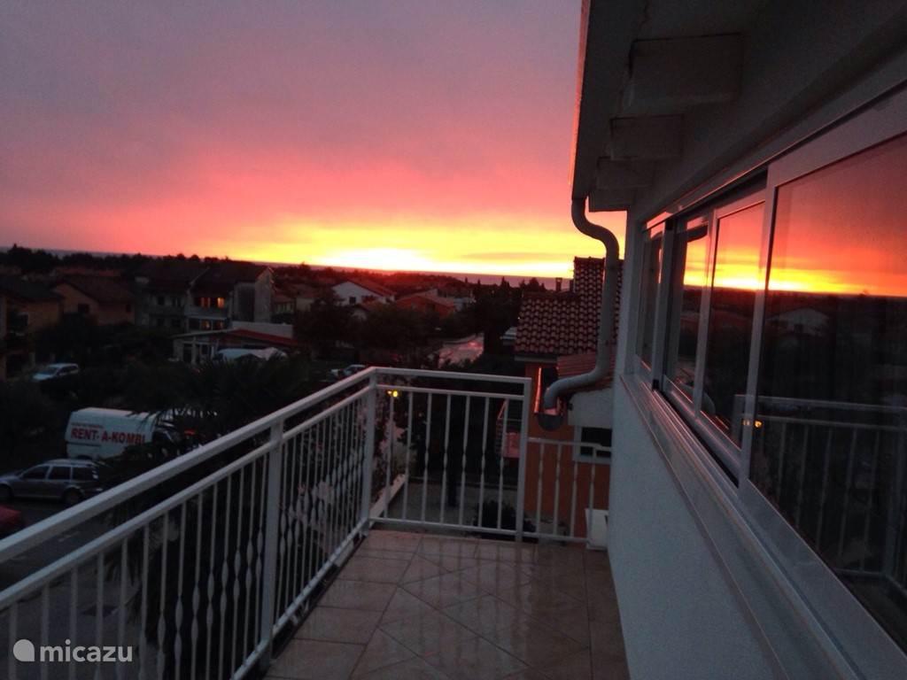 En vanaf het balkon een schitterende zonsondergang aanschouwen