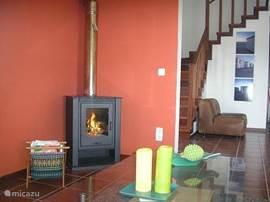 Gezellige ruime woonkamer met houtkachel. Vanuit de kamer heeft u toegang tot de veranda.