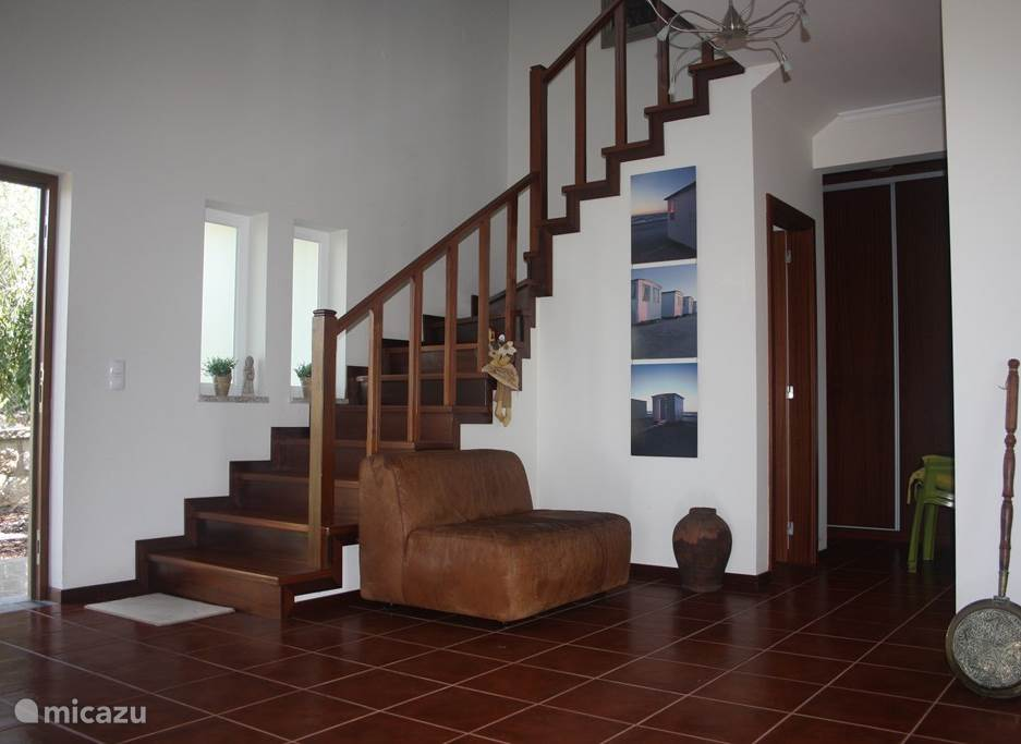 Ruime entree geeft toegang tot het huis. Onder de trap is een kast met de wasmachine.