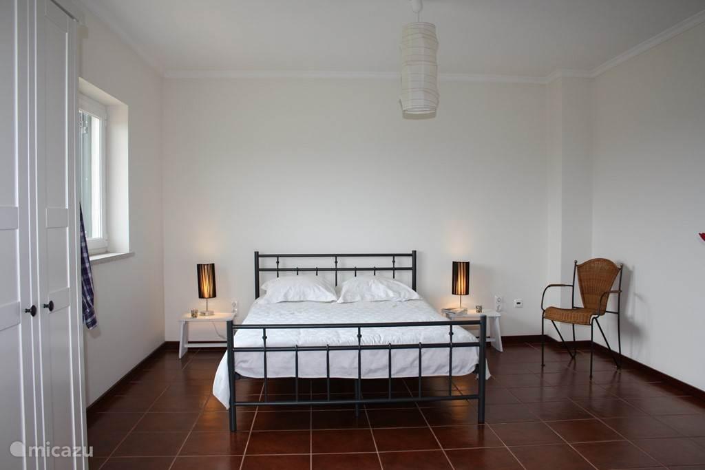 Ruime lichte slaapkamer met openslaande deuren naar balkon.