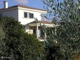 Het huis gezien vanaf het landweggetje. Vanaf het terras heeft u een prachtig uitzicht over de groene omgeving