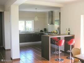 De ruime keuken wordt afgescheiden van de woonkamer door een hoge tafel (bar) met vier krukken. Heerlijk voor het ontbijtje.