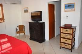 De master bedroom heeft ook een flatscreen tv en een inloopkast.