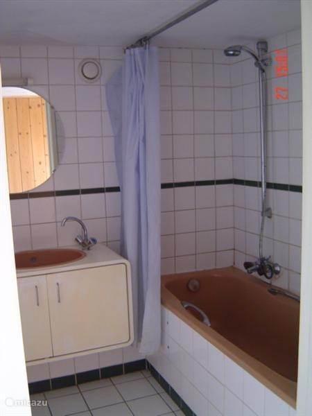 Badkamer met wastafel en bad