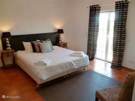 Master bedroom met balkon aan de voorzijde en begane grond aan de achterzijde.