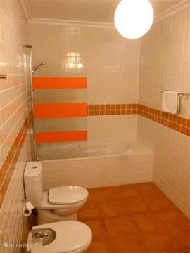 Badkamer met ligbad en dubbele wastafel.