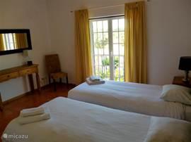 Slaapkamer met openslaande deur naar het balkon aan de voorzijde. Achterzijde is begane grond.