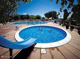 Het zwembad is gratis toegankelijk voor mijn gasten!  Kinderbad en op de achtergrond het grote zwembad van de camping.