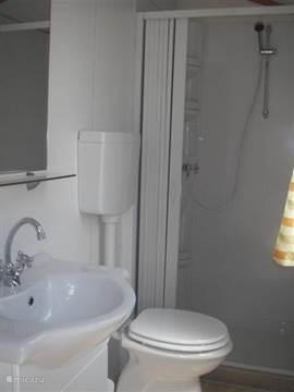 Badkamer met ruime douche, toilet, lavabo met spiegel en opbergkast. Bij uw boeking is er de mogelijkheid om een handdoekenpakket te reserveren.