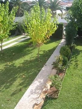 De tuin vanaf het terras. De bomen geven een heerlijke schaduw. 's Avonds wel opletten, want dan gaan de sproeiers aan!