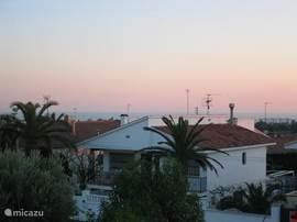Uitzicht vanaf het boventerras, palmbomen, villa's, de zee, vakantie.