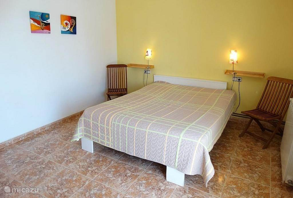 De gele slaapkamer (14,7 m2) boven. Ouder slaapkamer met eigen badkamer en openslaande deuren naar het balkon/terras.