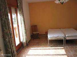 De oranje slaapkamer (21 m2) boven. Ook te gebruiken als tweede woonkamer. Met openslaande deuren naar het grote dakterras.
