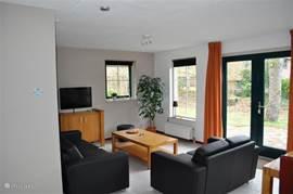 Nogmaals het zitgedeelte in de woonkamer met de openslaande deuren naar het terras.