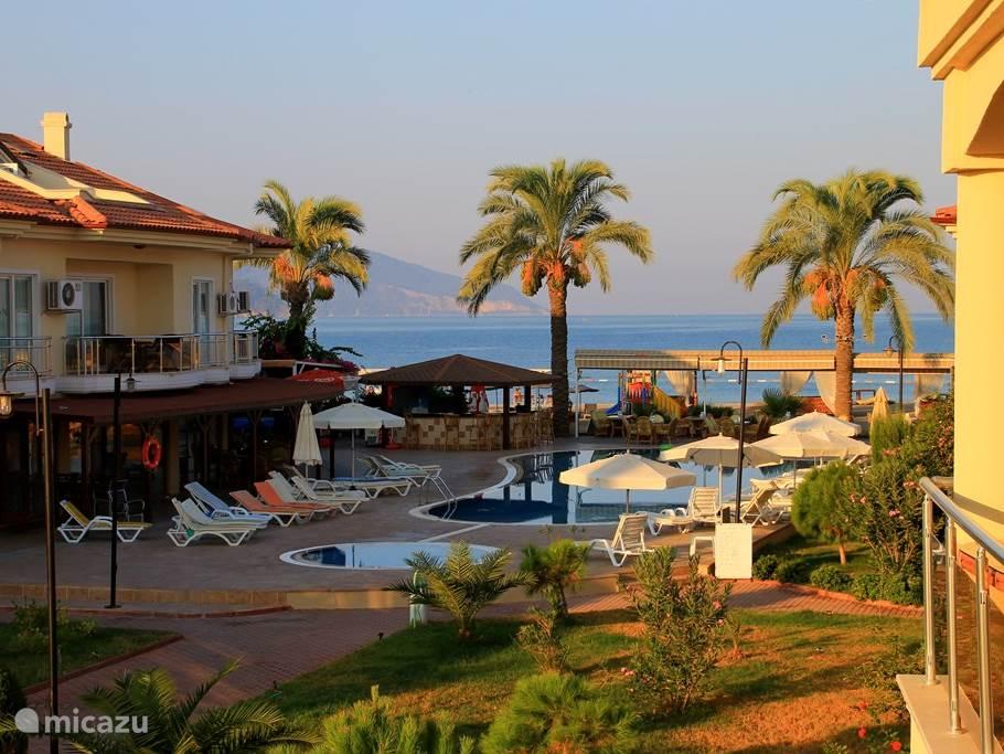 Fraai uitzicht vanaf het dakterras van Seahorse 8 richting zwembad met bar, strand en zee. U hoort de golven ruisen tegen de kust.