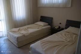 Tweepersoons slaapkamer 1e etage, met twee eenpersoonsbedden. Ook hier een Frans balkonnetje