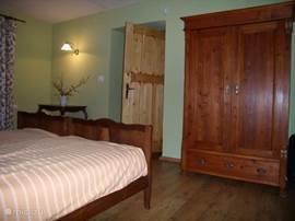 Tweepersoons slaapkamer met uitzicht op het erf, met zit hoekje.