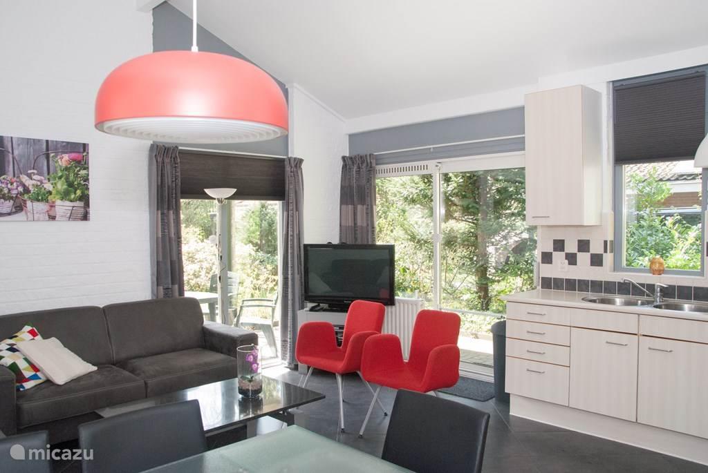Een blik in de gezellige woonkamer met een ruim bankstel en eethoek.