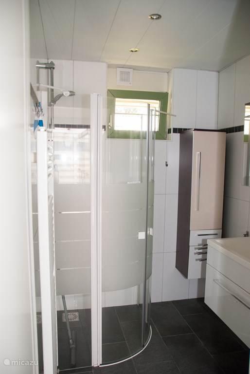Badkamer met douchehoek en wastafel.
